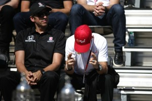 Helio Castroneves crosses his fingers when the announcer mentions that Castroneves is going for his fourth Indianapolis 500 win.